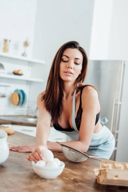 Sexy woman in underwear and blue apron holding eggs in kitchen stock vector