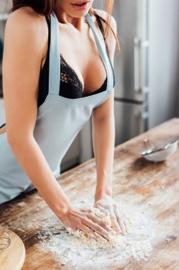 Partial view of sexy woman in underwear and blue apron kneading dough in kitchen