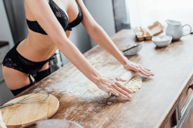 Partial view of sexy woman in black lingerie rolling out dough with rolling pin