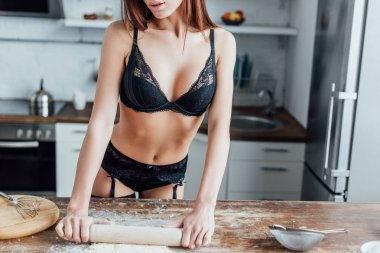 Cropped view of sexy woman in black lingerie rolling out dough with rolling pin