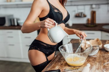 Cropped view of sexy girl in black lingerie whipping eggs with whisk and pouring milk