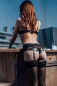 Vissza kilátás szexi lány fekete fehérnemű liszttel a bugyi álló konyhában
