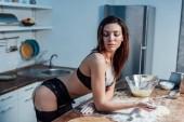 Szexi lány fekete fehérnemű a liszttel és a gördülő PIN a konyhában