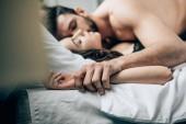 selektiver Fokus des leidenschaftlichen Mannes, der im Bett Hand in Hand mit der Frau liegt