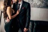 abgeschnittene Ansicht eines Mannes im Anzug, der neben einer Frau im schwarzen Kleid steht