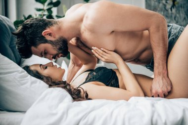 shirtless bearded man looking at attractive sexy woman on bed