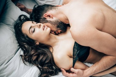 overhead view of shirtless bearded man undressing and kissing attractive sexy woman on bed
