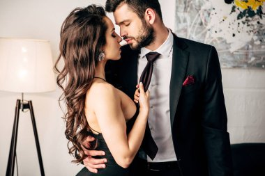 attractive girl in black dress holding tie of passionate man standing in suit