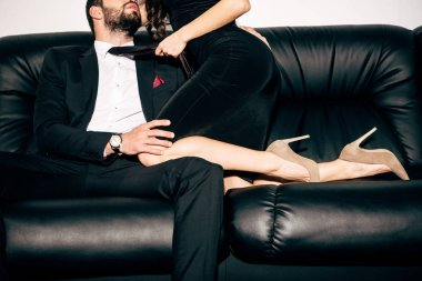 cropped view of sexy girl in black dress holding tie of bearded man sitting on sofa
