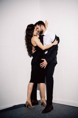 attractive brunette woman undressing handsome man near white wall