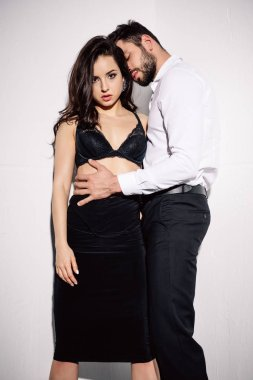 Sexy woman in black bra standing with handsome bearded man on white stock vector