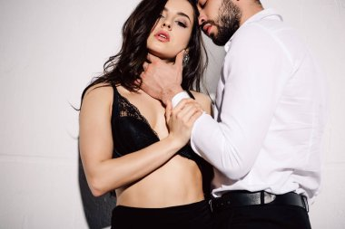 handsome man touching face of sexy brunette woman in black bra standing on white