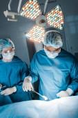 Krankenschwester und Chirurg in Uniformen und medizinischen Masken bei Operationen