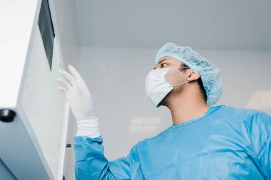 low angle view of doctor in medical mask looking at x-ray