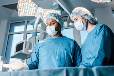 nurse in uniform and mask and doctor pointing with fingers in operating room