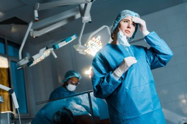 selective focus of nurse in uniform putting off medical mask in operating room