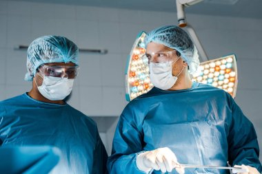 nurse and surgeon in uniforms and medical masks doing operation