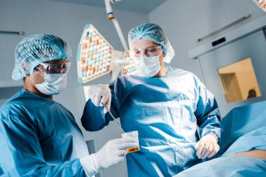 nurse and surgeon in uniforms and medical masks doing operation in operating room