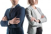Fotografia partial view of businesswoman and businessman standing shoulder to shoulder with crossed arms isolated on white