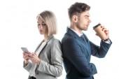 hezká žena, která používá telefon Smartphone, a pohledný muž popíjí kávu a stojí na zádech izolován na bílém