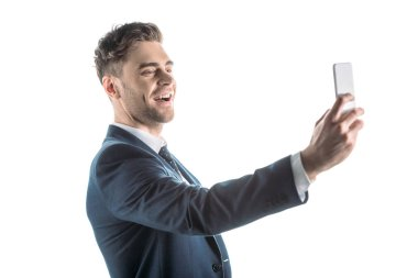 Handsome, cheerful businessman taking selfie with smartphone isolated on white stock vector