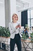 pretty smiling businesswoman in formal wear using smartphone in office