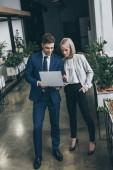 zwei junge lächelnde Geschäftspartner mit Laptop zusammen im Büro