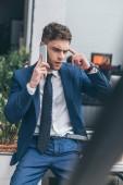 szelektív középpontjában gondolkodó üzletember beszél smartphone hivatalban