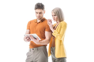 serious blonde woman and thoughtful handsome man using digital tablet together isolated on white