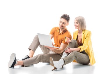 smiling handsome man with laptop and pretty woman with credit card sitting on white