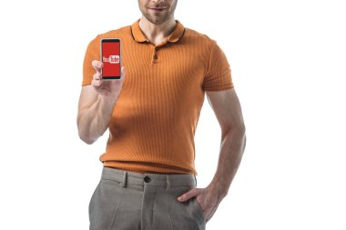 cropped view of man with hand in pocket holding smartphone with youtube app on screen isolated on white