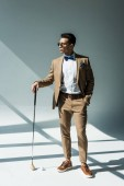 stylish mixed race man in suit posing with golf club on grey with sunlight