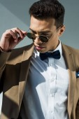 stylish mixed race man in suit and bow tie holding sunglasses while posing on grey with sunlight