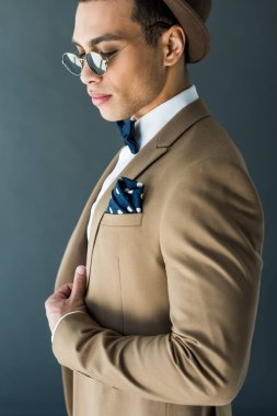 Fashionable mixed race man in suit and sunglasses posing isolated on grey stock vector