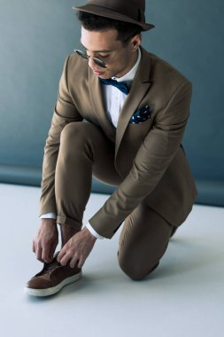 stylish mixed race man in suit and sunglasses putting on shoe on grey and white