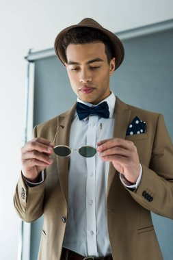 Stylish mixed race man in suit and bow tie holding sunglasses on grey stock vector
