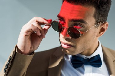Stylish mixed race man in suit and sunglasses posing on grey with red light stock vector