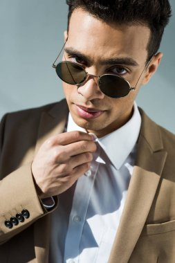 Stylish mixed race man in suit and sunglasses adjusting shirt and looking at camera isolated on grey stock vector