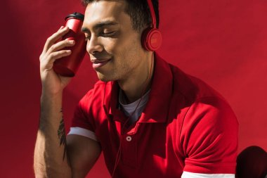 stylish mixed race man in headphones with eyes closed holding coffee to go on red