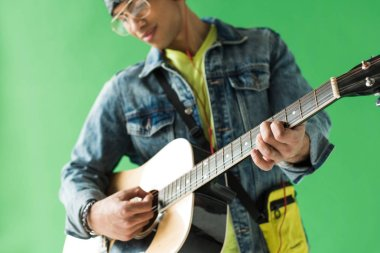 selective focus of mixed race man in denim playing acoustic guitar on green screen