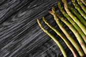 top view of organic green asparagus on wooden table