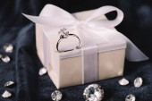 selective focus of engagement ring on gift box with bow near shiny diamonds on blue cloth