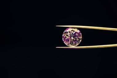 colorful pure sparkling diamond in tweezers isolated on black