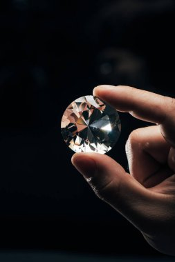 cropped view of man holding big clear shiny diamond on black background