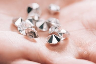 close up of shiny small pure diamonds in hand