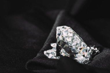 sparkling pure big diamond among small on black textured shiny cloth