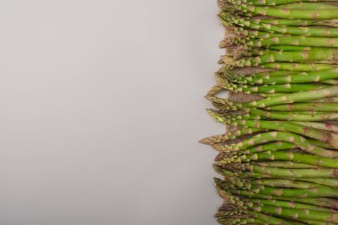 top view of green asparagus scattered on sackcloth on grey background
