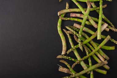 top view of green uncooked asparagus scattered on black background