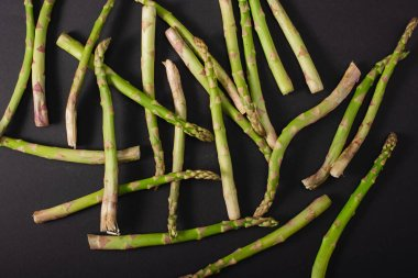 top view of green raw asparagus scattered on black background