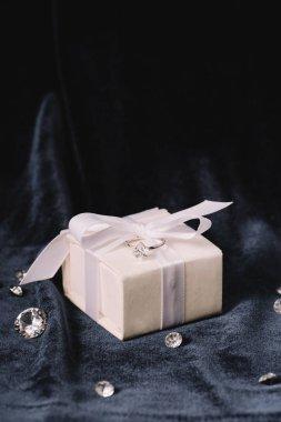 engagement ring on gift box near shiny diamonds on blue cloth